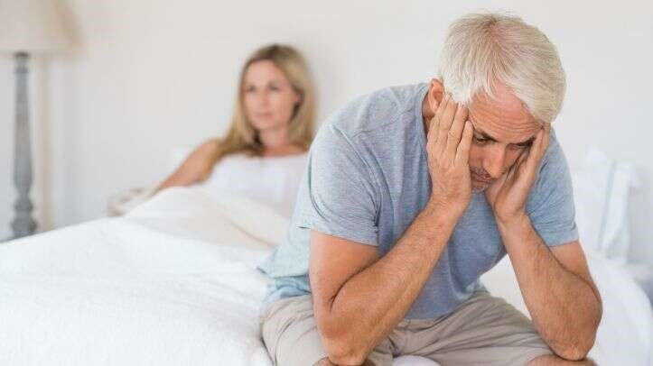man sat at end of bed embarrised from erectile dysfunction