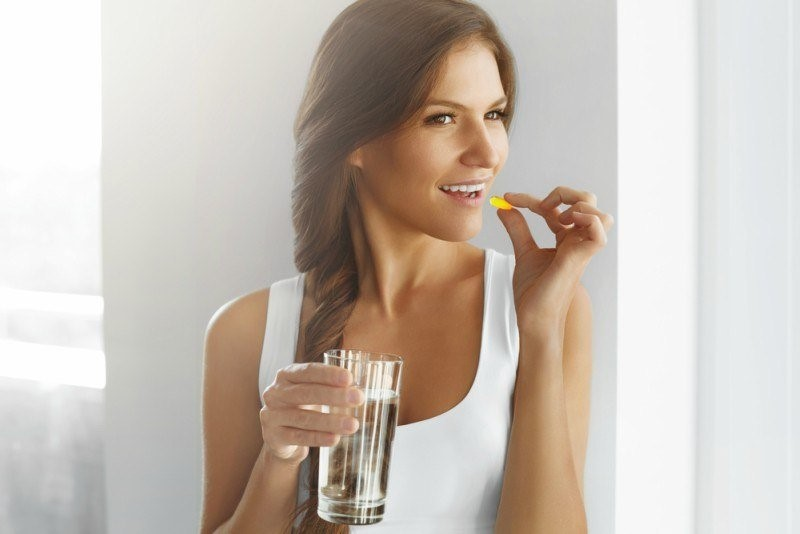A women taking a pill with a glass of water