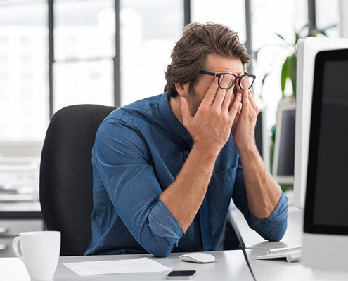 A man working in an office rubbing his eyes because he is tired at work