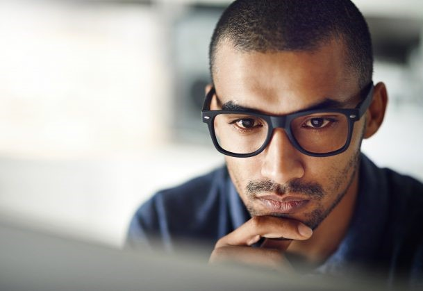 A man focussed and looking at his computer screen