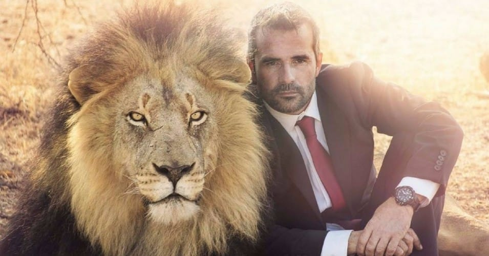 Man sat next to a lion